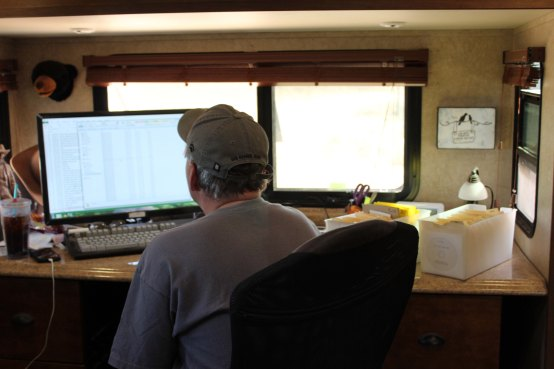 Lee working on his spreadsheet. The window looks out on the gate